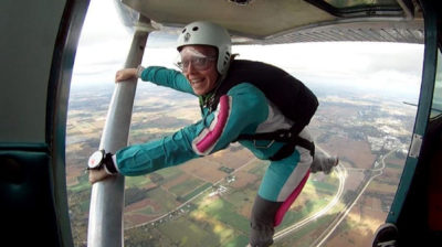 Christie Munn hanging off the wing during a skydive at Wisconsin Skydiving Center