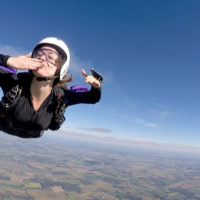 Woman blowing a kiss as she skydives solo at Wisconsin Skydiving Center near Milwaukee, WI
