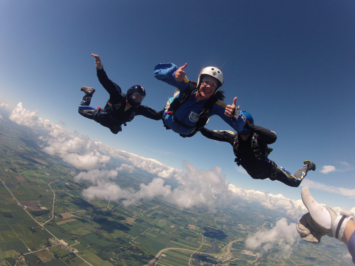 An AFF skydiving student gives two thumbs up during free fall while being assisted by two skydiving instructors.