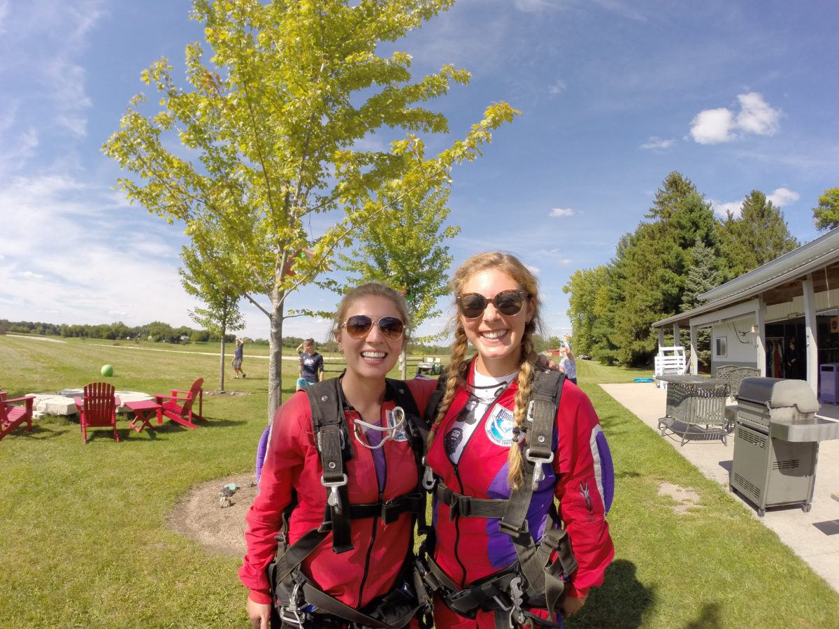 Two girls suited up in red jumpsuits preparing to skydive at Wisconsin Skydiving Center near Milwaukee, WI