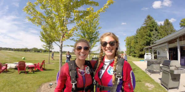 Two ladies suited up in red jumpsuits preparing to skydive.