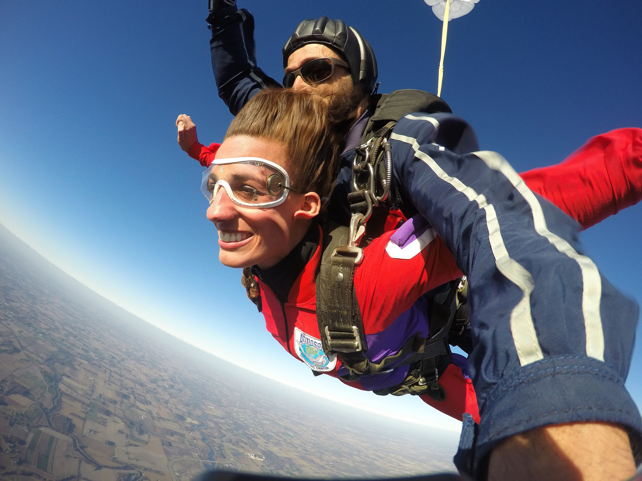 A lady smiles while in free fall during a tandem skydive.