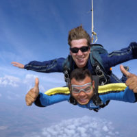 A man with a big smile holds gives a thumbs up in free fall.