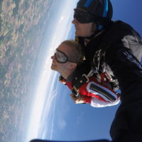 A girl holds on to her harness right after leaving the plane at Wisconsin Skydiving Center near Milwaukee, WI