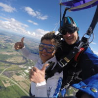 A lady gives two thumbs up while smiling at the camera enjoying her parachute ride.