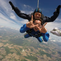 A man in free fall makes the 'W' sign with his fingers in free fall at Wisconsin Skydiving Center near Madison, WI