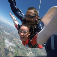 A girl smiles and spreads her arms out during free fall.