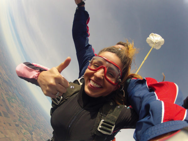 woman gives a thumbs up in skydiving freefall
