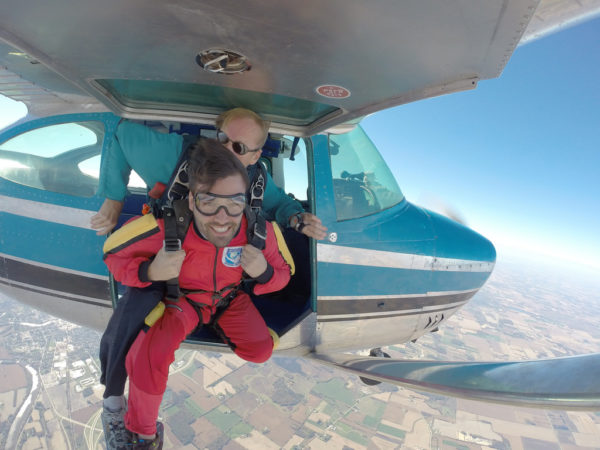 man looks up before exiting skydiving plan
