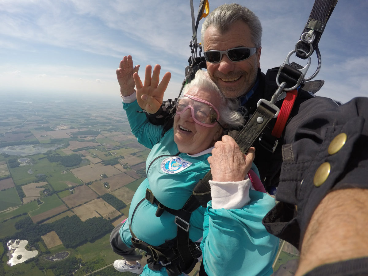 Bo Babovic smiles at the camera 4000 feet in the air suspended under canopy with his tandem student, Anna Mae