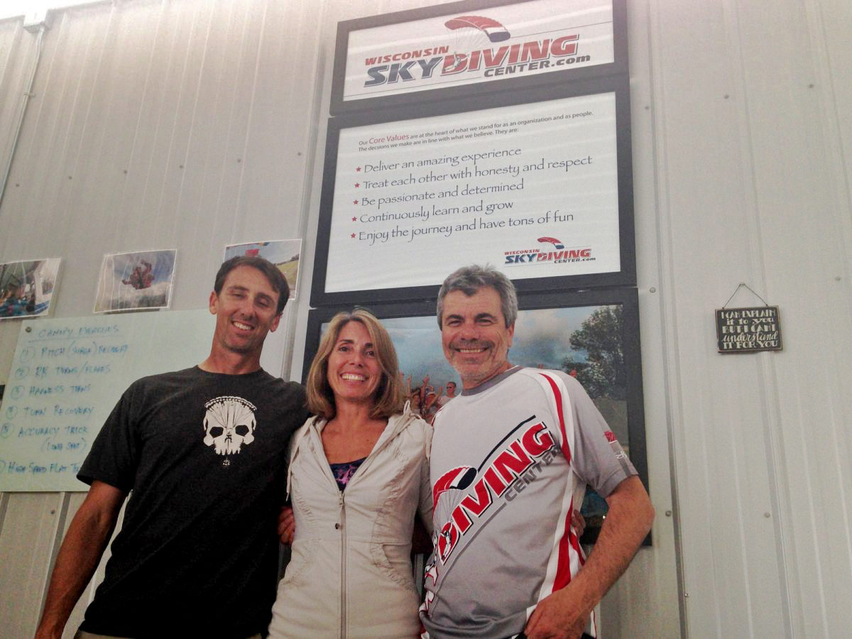 Alex and Bo in front of Wisconsin Skydiving Center Core Values sign