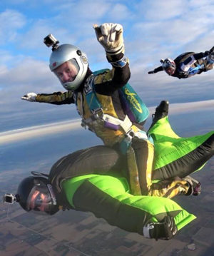 Skydiving instructor Laura Duffy riding a fellow wingsuit skydiver