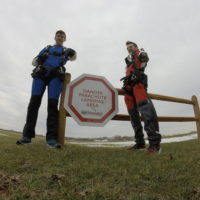 Two guests pose for a picture near the 'No Skydivers Beyond This Point' sign