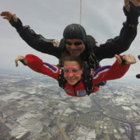A tandem student gives a thumbs up and smiles during free fall.