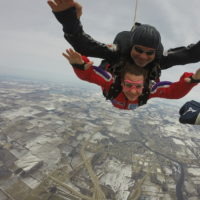 A tandem student smiles while in free fall.