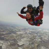 A tandem student smiles while making a tandem skydive