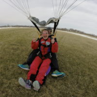 A tandem student in red jumpsuit lands with her instructor from a tandem skydive.