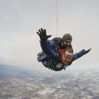 A tandem student spreads his arms during a tandem skydive.