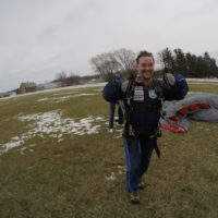 A tandem student runs in excitement after landing from a tandem skydive.