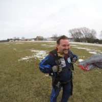 A tandem student smiles excitedly after landing from a tandem skydive.