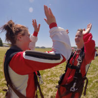 Two solo skydiver high five each other after landing at Wisconsin Skydiving Center near Milwaukee, WI