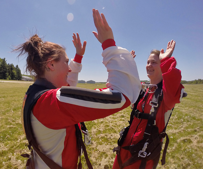 Two solo skydiver high five each other after landing