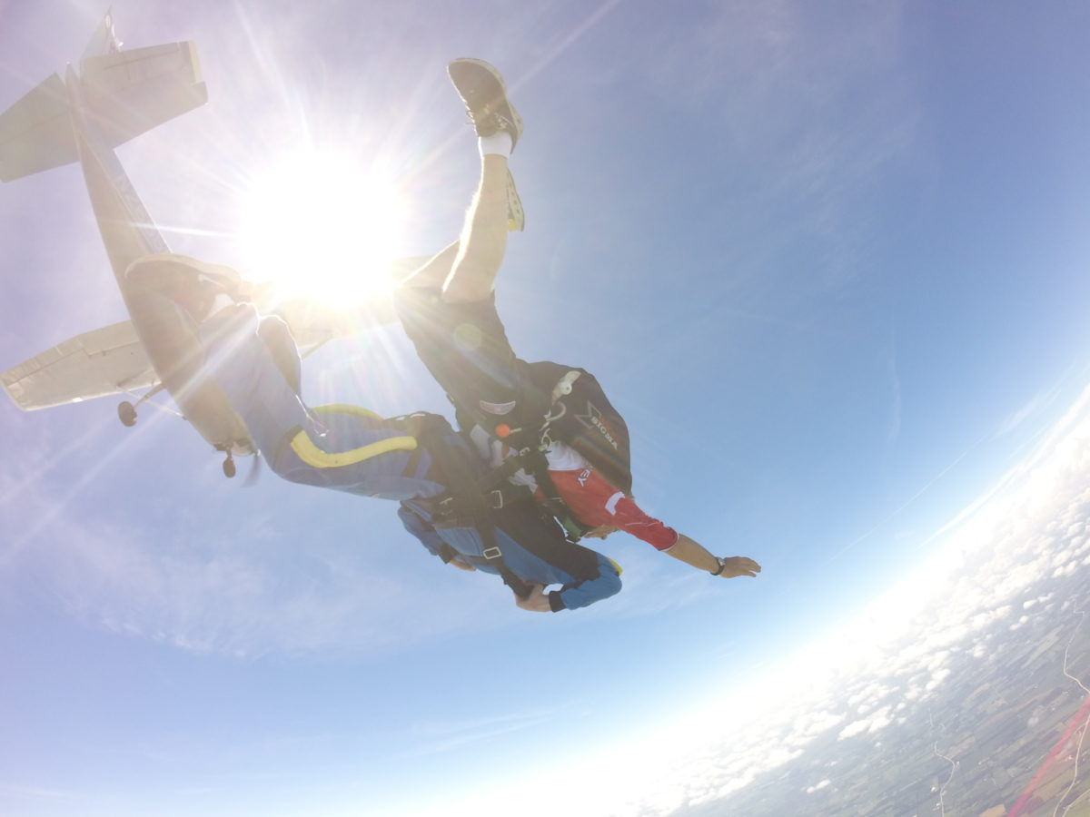Asking when does skydiving season start near Milwaukee, Wisconsin as tandem skydivers jump from a plane