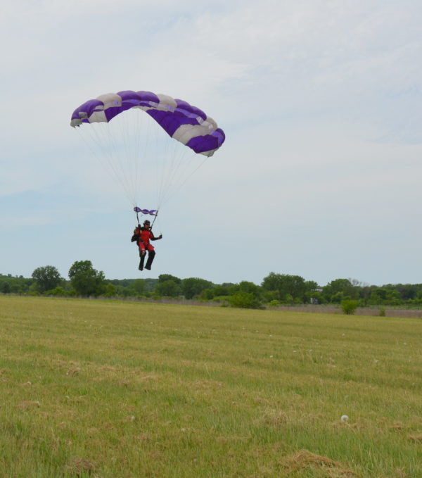 A skydiver with an open parachute about to land in a large grassy area.