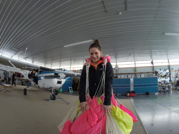 A young lady packing her parachute and preparing for a skydive in the hangar at Wisconsin Skydiving Center