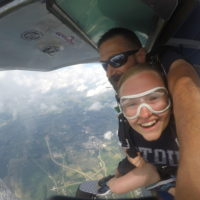 A tandem student smiles right before exiting the Cessna 182 at 12,000 feet