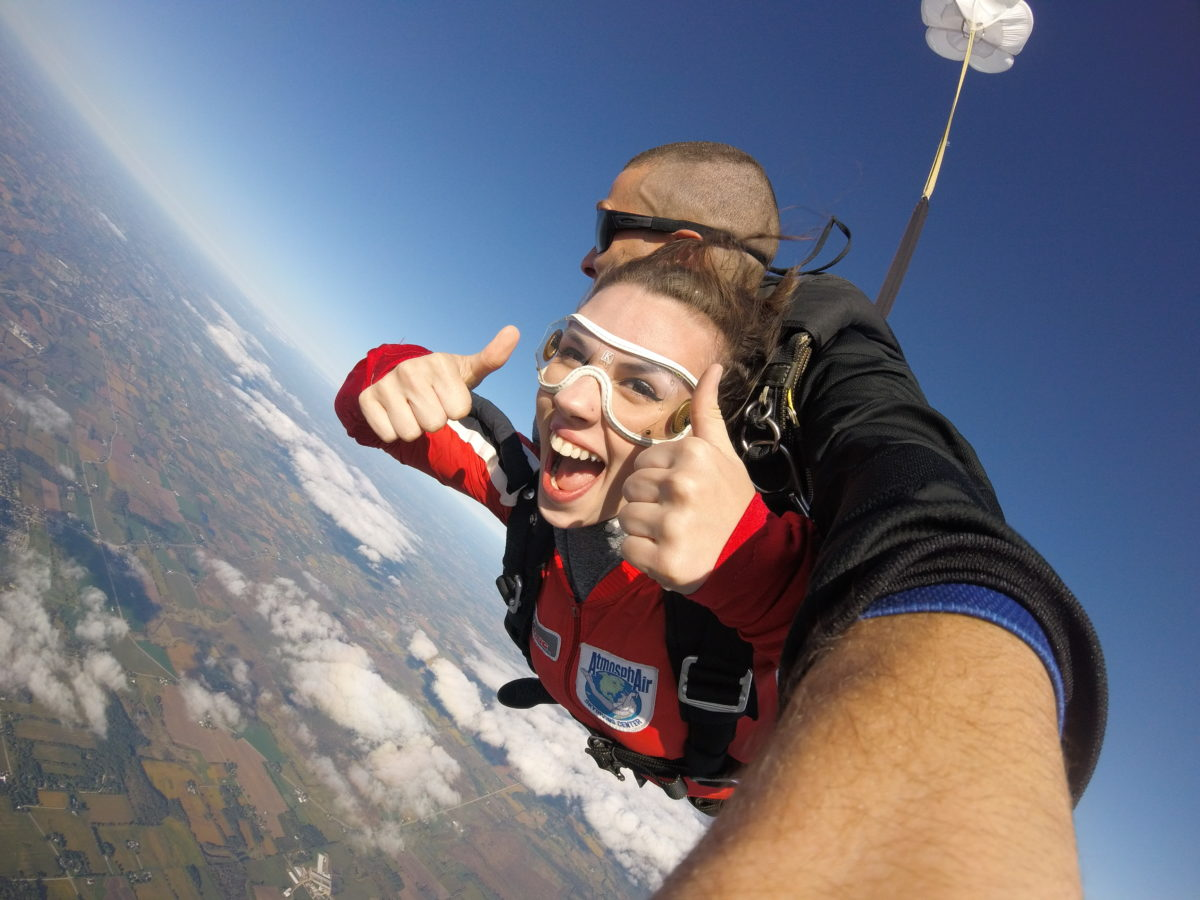 First-time skydiver giving a thumbs up during her tandem skydive at Wisconsin Skydiving Center near Milwaukee