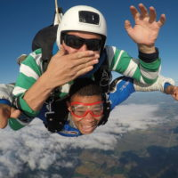 Tandem skydiver giving thumbs up and instructor blowing a kiss at Wisconsin Skydiving Center near Milwaukee