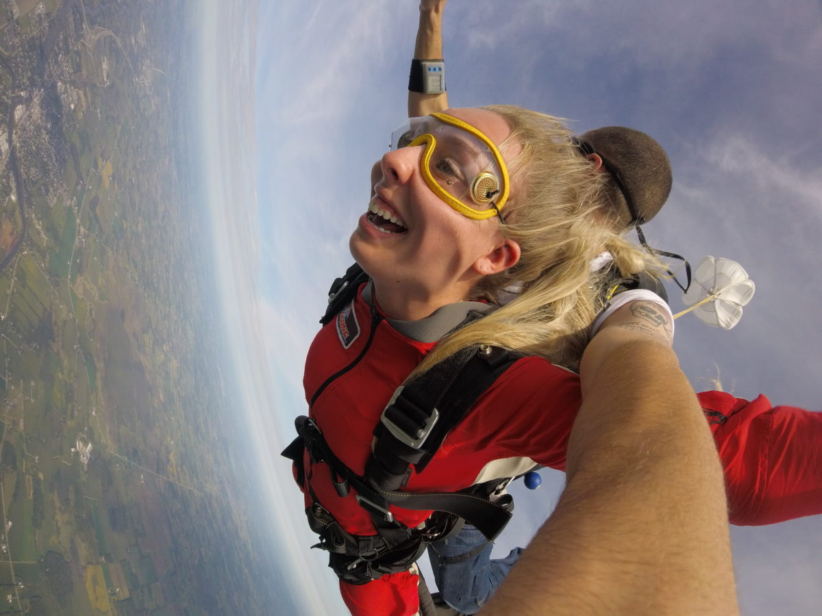 a young lady smiles during the free fall of her tandem skydive