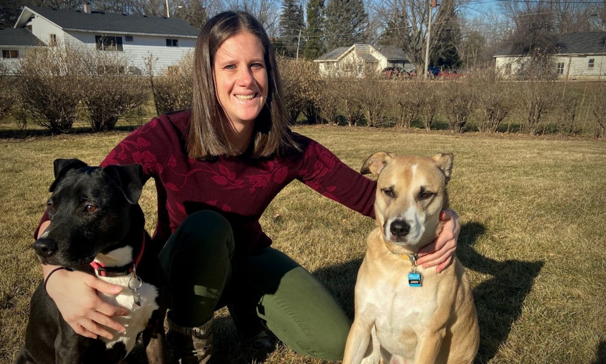 Erica smiles with her two dogs