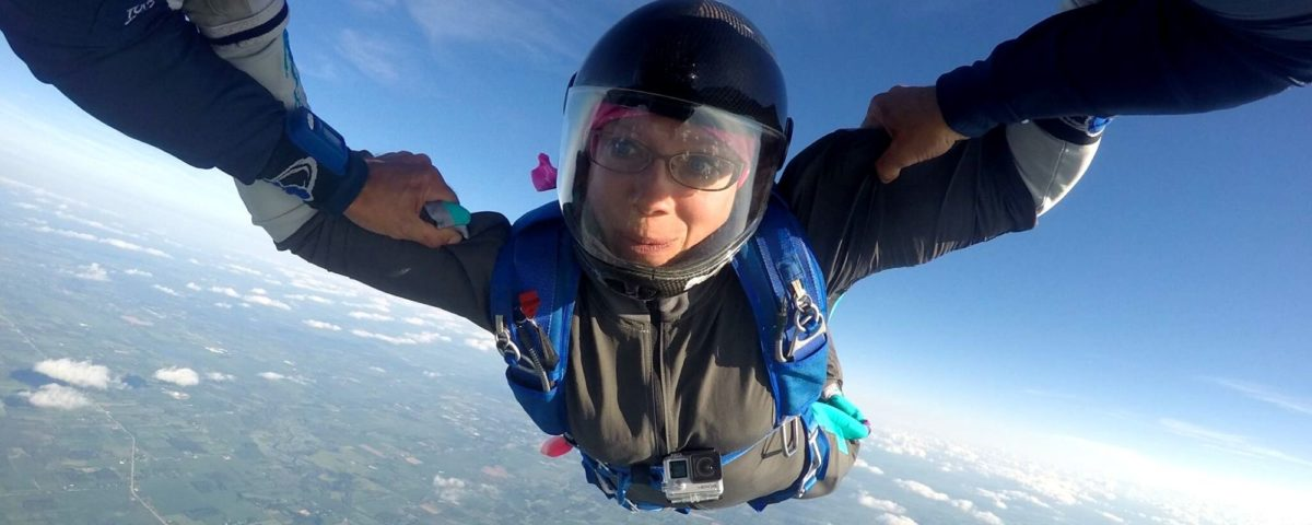 A professional skydiver wearing glasses and a full-face helmet while skydiving at Wisconsin Skydiving Center near Chicago