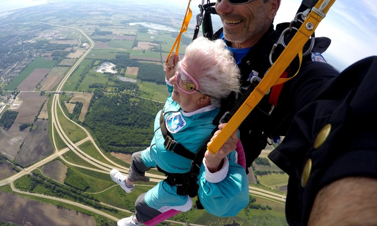 Anna Mae smiles while flying under parachute with tandem instructor, Bo