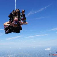 A tandem skydiving pair showing great happiness in free fall.