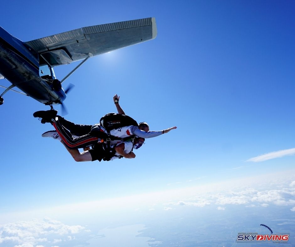 A tandem instructor and his student arch as they leave the plane.