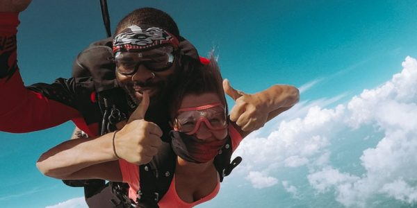 Woman in cute skydiving outfit giving thumbs up during a tandem skydive at Wisconsin Skydiving Center