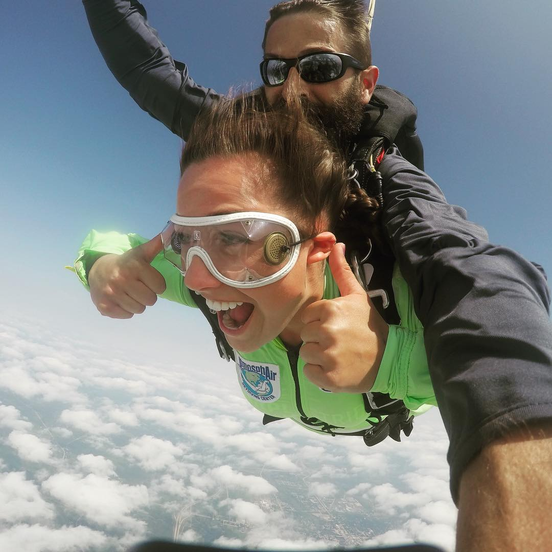 Girl smiling and giving thumbs up during her first skydive at Wisconsin Skydiving Center near Madison